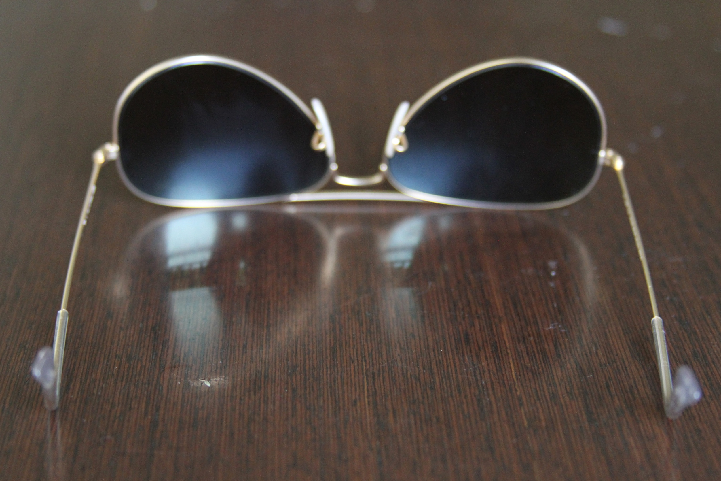 d3953c8efb Hold the arms of your sunglasses with your thumbs facing each other (as in  the picture below). Gently push in the earpiece inward.